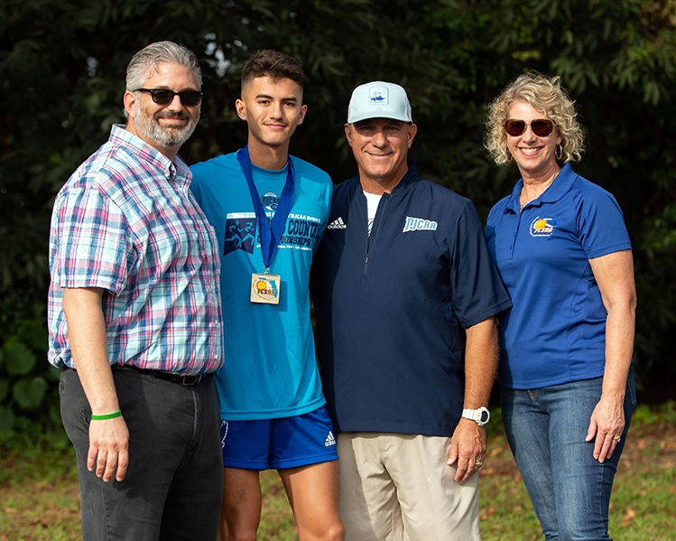Cross Country Runner Alexander Croy stands with Athletic Director Mike Matulia and representatives from NJCAA/FCSAA