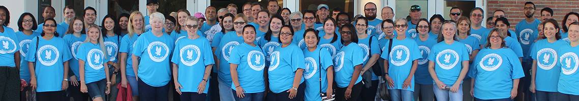 group photo of people wearing blue shirts with service day logo