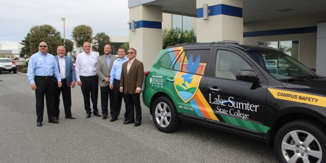 6 men posing next to van with Lake Sumter logo on it