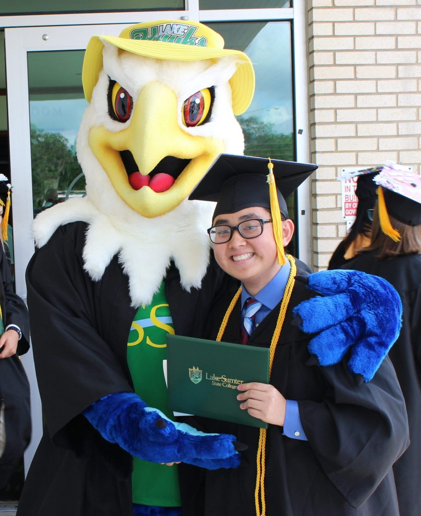 Mascot swoop with a LSSC graduate holding a diploma both wearing a cap and gown