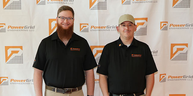 Two men posing in front of backdrop
