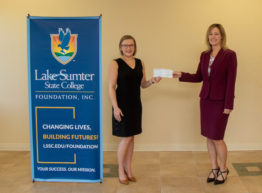 Alise Morris hands a check to Dr. Laura Byrd