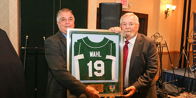 Pete Wahl and Dr. Sidor standing with Mr. Wahl's award frame