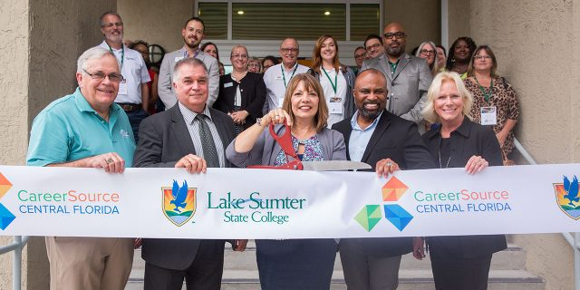 CareerSource and LSSC execs stand in a ribbon cutting line with woman in middle holding scissors