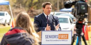 Florida Governor Ron DeSantis speaks at a podium with cars lined up for vaccinations behind him and news cameras facing him
