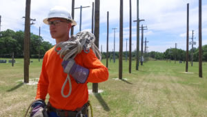 Man walking near utility poles with a hard hat and gear