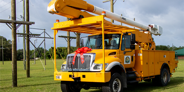 Yellow bucket truck with red bow on the hood