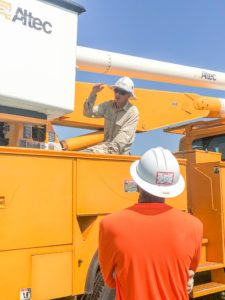 Man in hard hat sits on yellow utility truck explains something to student looking up at him