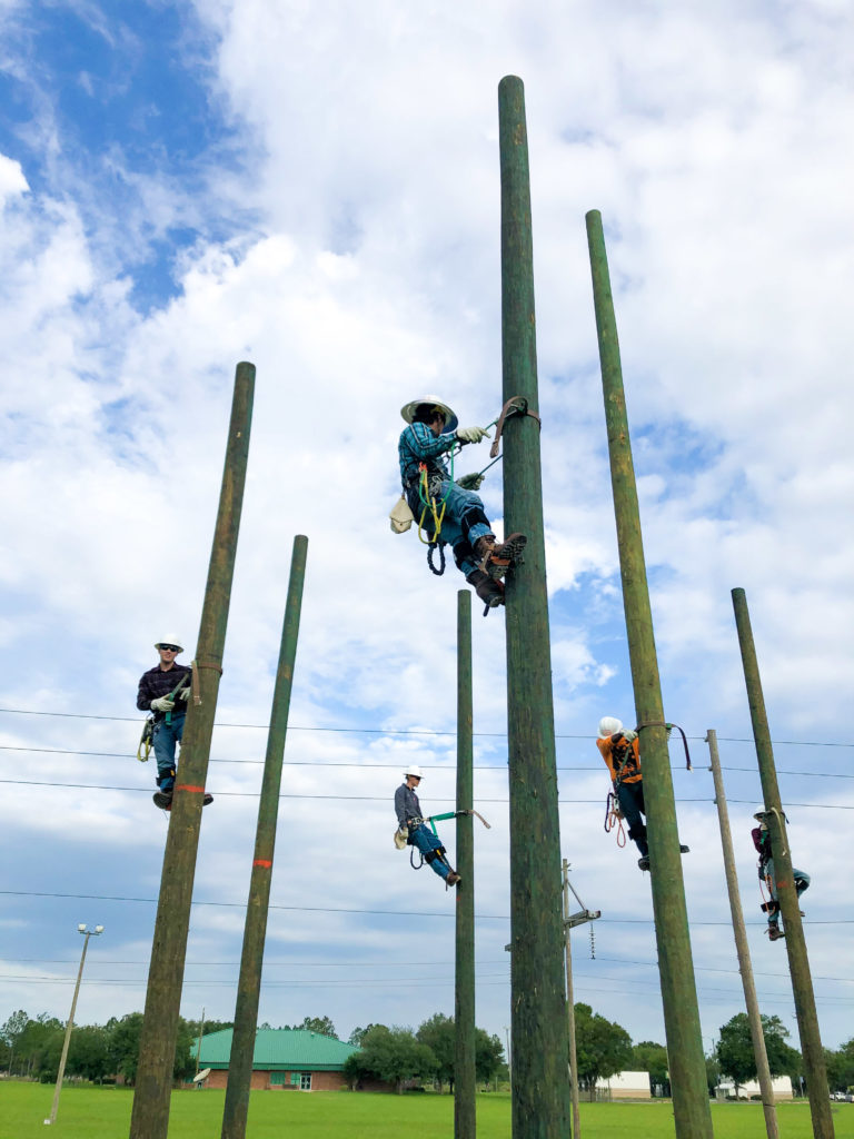 Lineworker students climbing on their utility poles