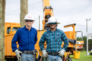 Two lineworker students pose for a photo in front of a yellow utility truck
