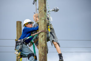 Lineworker student performs a pole top rescue with weighted mannequin