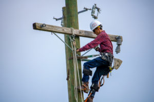 Lineworker student works atop the utility poles