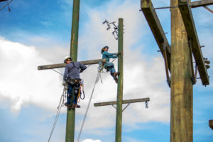 Lineworker worker students work atop utility poles