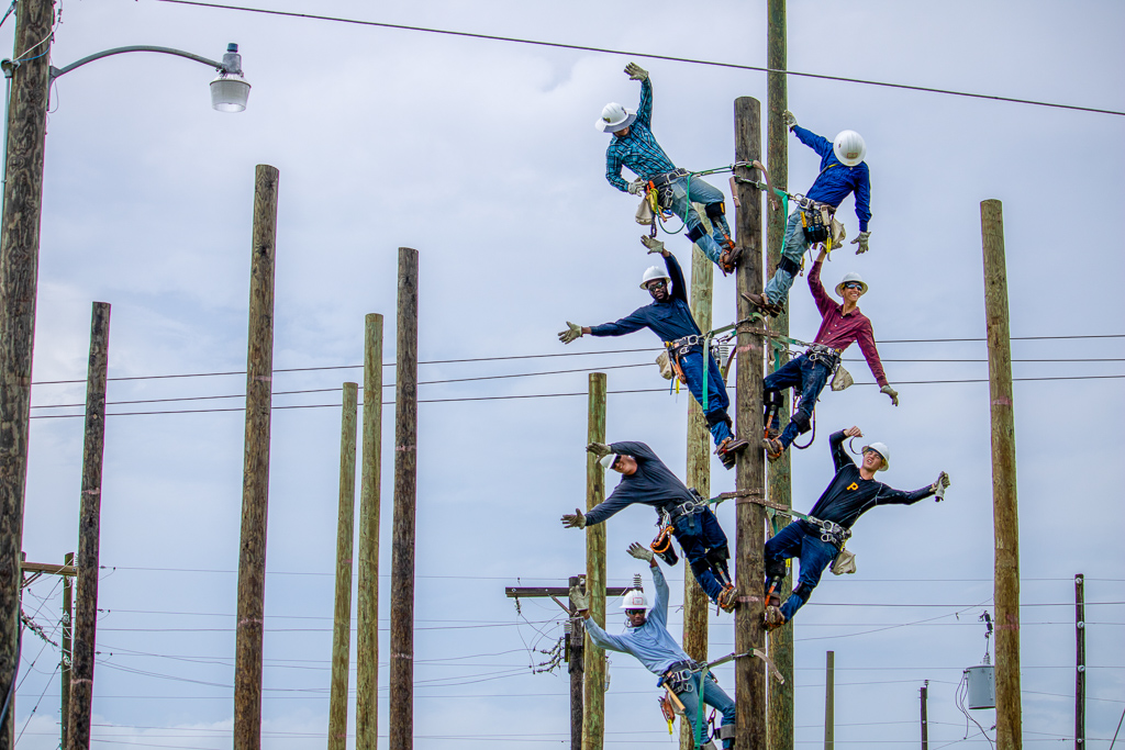 Seven lineworker students on one utility pole celebrating their completion of the program