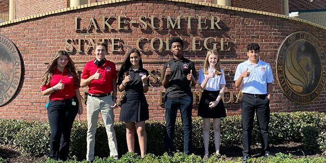Group of students standing in front of brick Lake-Sumter State College sign showing thumbs up