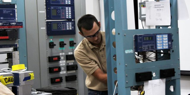 Man in khaki colored polo working on a free-standing protective relay equipment