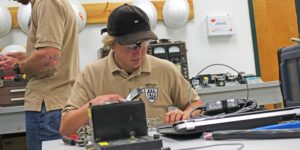 Man in a khaki colored shirt working on wiring while sitting at a table
