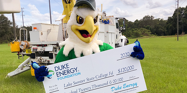 Swoop the Lakehawk holding an oversized $120,000 check from Duke Energy with a utility truck in the background