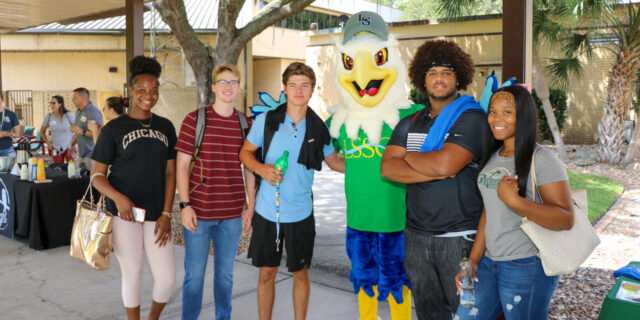 Students pose for a photo with Swoop the Lakehawk in the middle