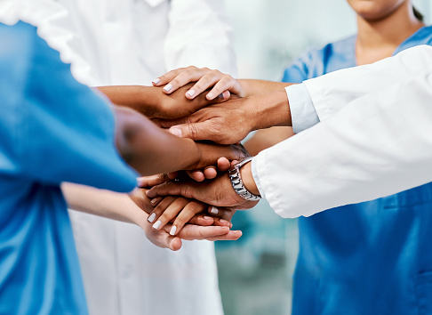 Closeup shot of a group of medical practitioners joining their hands together in a huddle