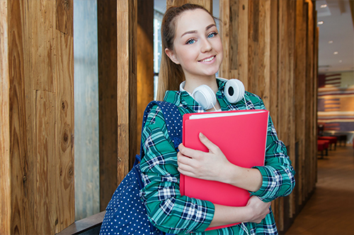 Woman holding a red binder and smiling
