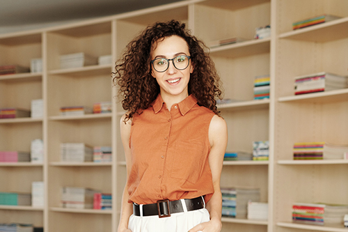 Woman in an orange dress shirt standing in front of bookshelves