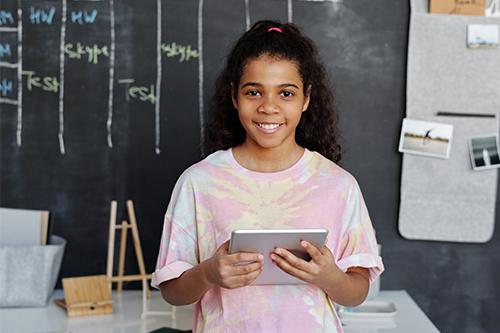 Girl in a tie-dye shirt holding an iPad in front of blackboard