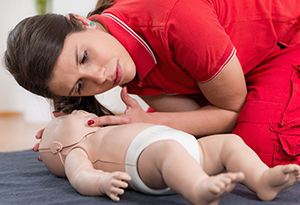 Woman giving CPR to a baby doll during training